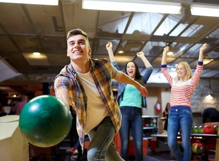 Foto de people, leisure, sport and entertainment concept - happy young man throwing ball in bowling club - Imagen libre de derechos