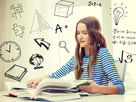 Foto de education and home concept - smiling student girl sitting at table and reading books - Imagen libre de derechos