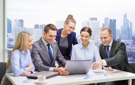 Photo for business, technology, teamwork and people concept - smiling business team with laptop computers, documents and coffee having discussion over office background - Royalty Free Image