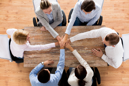 Photo for business, people, cooperation and team work concept - close up of creative team sitting at table and holding hands on top of each other in office - Royalty Free Image