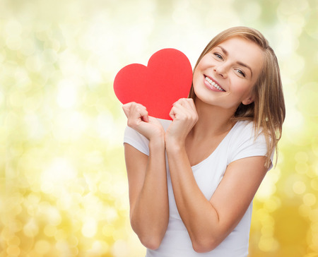 Foto de happiness, health, people, holidays and love concept - smiling young woman in white t-shirt holding red heart over yellow lights background - Imagen libre de derechos