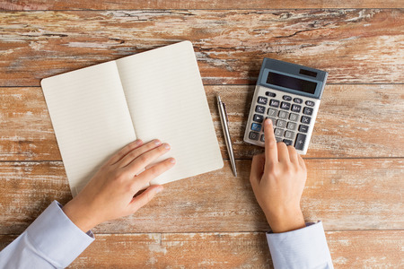 Photo pour business, education, people and technology concept - close up of female hands with calculator, pen and notebook on table - image libre de droit