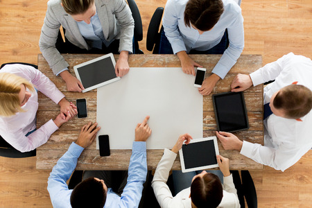 Foto de business, people, technology and team work concept - close up of creative team with, blank paper smartphones and tablet pc computers sitting at table in office - Imagen libre de derechos