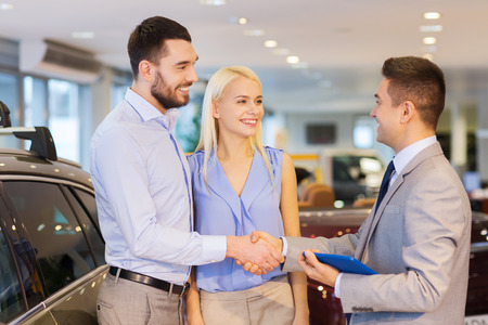 Photo pour auto business, car sale, technology, gesture and people concept - happy couple with car dealer shaking hands in auto show or salon - image libre de droit