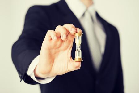 Photo pour close up of man hand holding hourglass. - image libre de droit