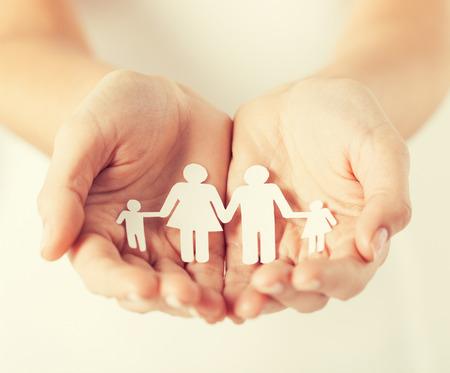 Foto de close up of womans cupped hands showing paper man family - Imagen libre de derechos
