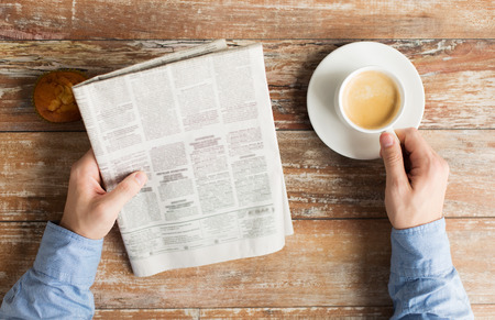 Foto de close up of male hands with newspaper, muffin and coffee cup on table - Imagen libre de derechos