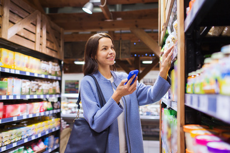 Photo for happy young woman with smartphone choosing and buying food in market - Royalty Free Image