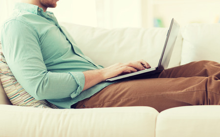 Foto de close up of man working with laptop computer and sitting on sofa at home - Imagen libre de derechos