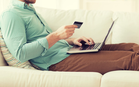 Photo pour close up of man with laptop computer and credit card at home - image libre de droit