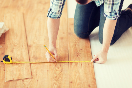 Foto de close up of male hands measuring wood flooring - Imagen libre de derechos