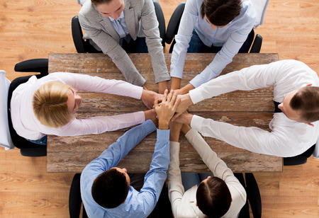 Photo pour business, people, cooperation and team work concept - close up of creative team sitting at table and holding hands on top of each other in office - image libre de droit