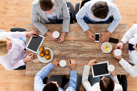 Foto de business, people, break and team work concept - close up of creative team meeting and drinking coffee with muffins during lunch in office - Imagen libre de derechos