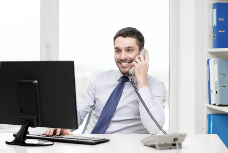 Foto de office, business, education, technology and internet concept - smiling businessman or student with computer and phone - Imagen libre de derechos