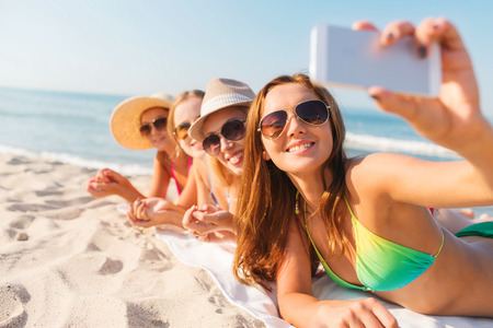 Foto de summer vacation, travel, technology and people concept - group of smiling women in sunglasses and hats making selfie with smartphone on beach - Imagen libre de derechos