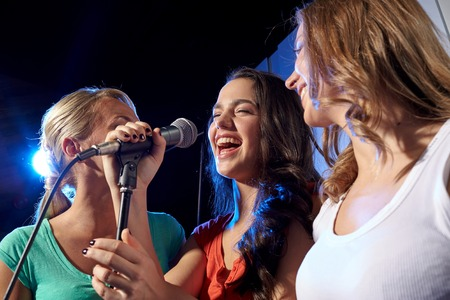 Photo for party, holidays, celebration, nightlife and people concept - happy young women singing karaoke in night club - Royalty Free Image