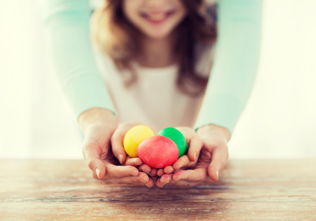 Photo for easter, family, holiday and child concept - close up of little girl and mother holding colored eggs - Royalty Free Image