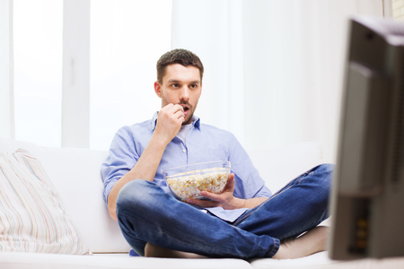 Foto de sports, food, happiness and people concept - man watching tv and eating popcorn at home - Imagen libre de derechos