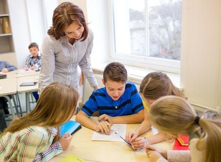 Foto de teacher helping school kids writing test in classroom - Imagen libre de derechos