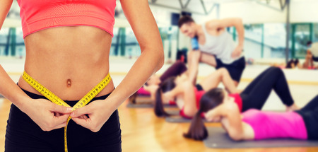 Photo pour diet, sport, fitness and heath concept - close up of female hands measuring waist with measuring tape - image libre de droit