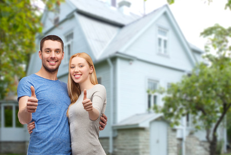 Photo for smiling couple hugging and showing thumbs up over house background - Royalty Free Image