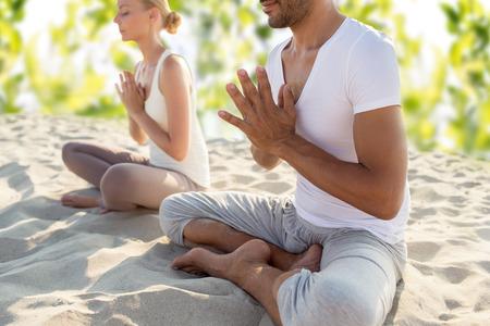 Photo pour smiling couple making yoga exercises sitting outdoors - image libre de droit