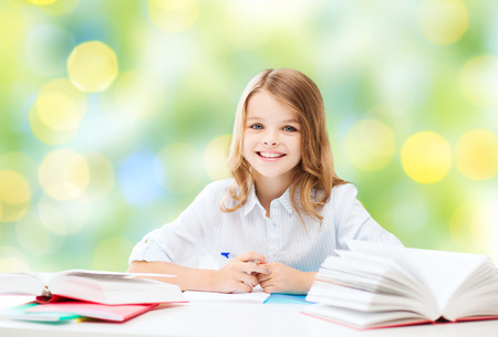 Photo pour happy student girl sitting at table with books and writing in notebook over green lights background - image libre de droit