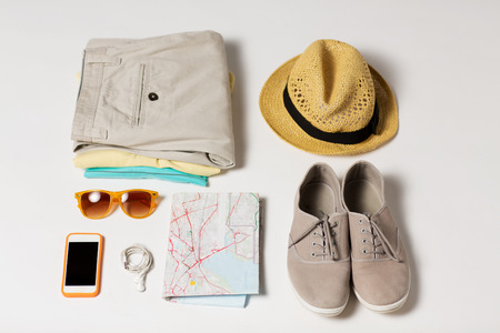 Foto de summer vacation, tourism and objects concept - close up of clothes, smartphone, personal stuff and travel map - Imagen libre de derechos