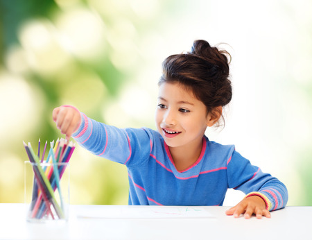 Photo for children, creativity and happy people concept - happy little girl drawing with coloring pencils over green background - Royalty Free Image