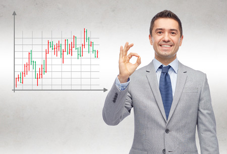 Foto de business, people, gesture and financial success concept - happy smiling businessman in suit showing ok hand sign over gray background with forex chart - Imagen libre de derechos