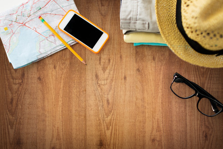 Foto de travel, summer vacation, tourism and objects concept - close up of folded clothes, smartphone and touristic map on wooden table - Imagen libre de derechos
