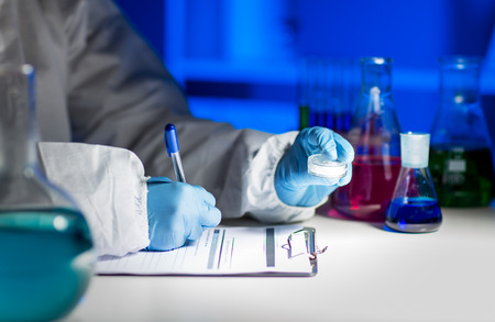 Foto de science, chemistry, medicine and people concept - close up of young scientist with chemical sample taking notes on clipboard and making test or research in laboratory - Imagen libre de derechos