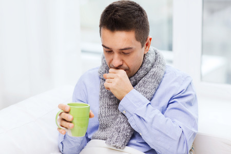 Photo pour healthcare, people and medicine concept - ill man with flu coughing and drinking hot tea from cup at home - image libre de droit