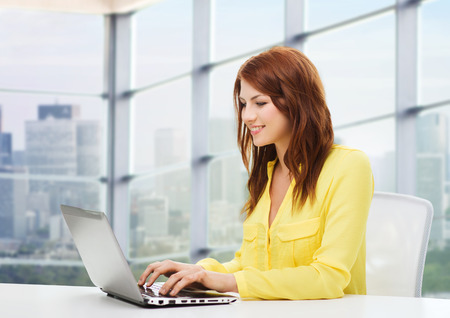Foto de people, business and technology concept - smiling young woman with laptop computer sitting at table over office window background - Imagen libre de derechos