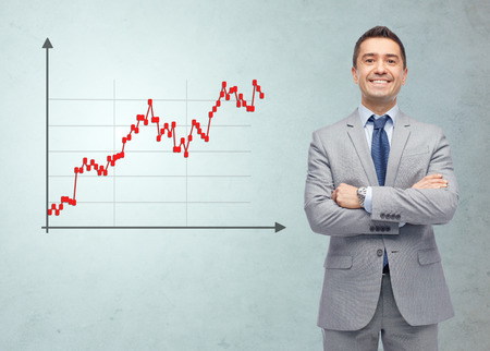 Photo pour business, people, economics, stock market and finances concept - happy smiling businessman in suit with forex chart over gray background - image libre de droit