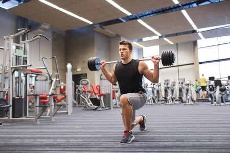 Photo for sport, bodybuilding, lifestyle and people concept - young man with barbell flexing muscles and making shoulder press lunge in gym - Royalty Free Image