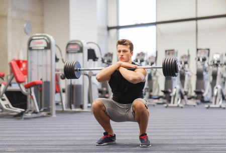 Foto per sport, bodybuilding, lifestyle and people concept - young man with barbell doing squats in gym - Immagine Royalty Free