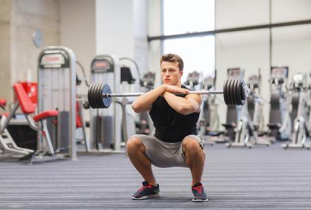 Foto de sport, bodybuilding, lifestyle and people concept - young man with barbell doing squats in gym - Imagen libre de derechos