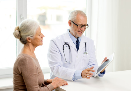 Photo for medicine, age, health care and people concept - smiling senior woman and doctor with tablet pc computer meeting in medical office - Royalty Free Image