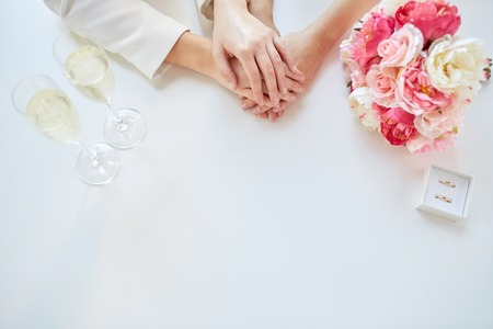 Photo for close up of happy couple hands with flower bunch, champagne glasses and wedding rings - Royalty Free Image