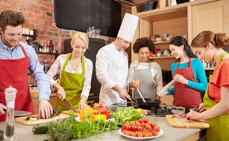 Foto per cooking class, culinary, food and people concept - happy group of friends and male chef cook cooking in kitchen - Immagine Royalty Free