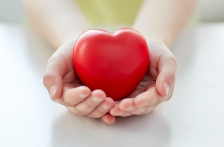Foto de people, love, charity and family concept - close up of child hands holding red heart shape at home - Imagen libre de derechos