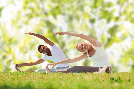 Foto de fitness, sport, yoga and people concept - happy couple stretching on mats over green tree leaves background - Imagen libre de derechos