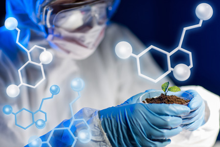 Foto de science, biology, ecology, research and people concept - close up of young scientist holding petri dish with plant and soil sample in bio laboratory over molecular structure - Imagen libre de derechos