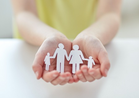 Foto de people, charity and care concept - close up of child hands holding paper family cutout at home - Imagen libre de derechos