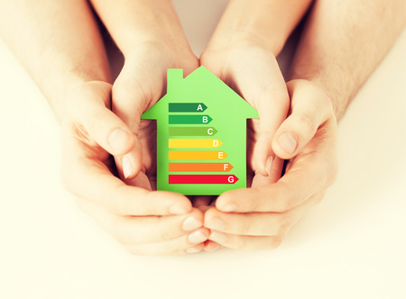 Foto de energy saving, real estate and family home concept - closeup of couple hands holding green paper house with energy efficiency rating - Imagen libre de derechos