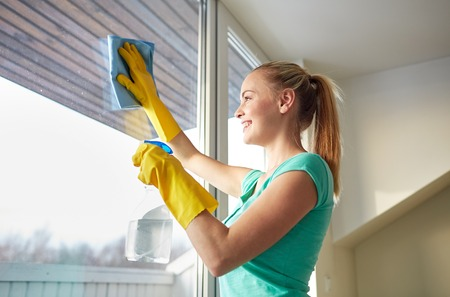 Foto de people, housework and housekeeping concept - happy woman in gloves cleaning window with rag and cleanser spray at home - Imagen libre de derechos