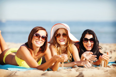 Photo for summer holidays and vacation - girls sunbathing on the beach - Royalty Free Image