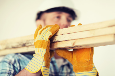 Foto de repair, building and home concept - close up of male in gloves and helmet carrying wooden boards on shoulder - Imagen libre de derechos