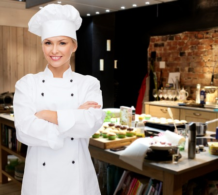 Foto de cooking, bakery, people and food concept - smiling female chef, cook or baker with crossed arms over restaurant kitchen background - Imagen libre de derechos